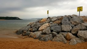 Danger Signs on Rocks on a Beach in Santander royalty free stock photos