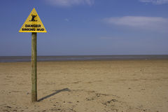 Danger sinking mud sign, sand point beach England uk. Horizontal royalty free stock photo