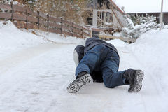 Danger Slipping - Accident danger in winter. A man has slipped and has fallen down Royalty Free Stock Photo