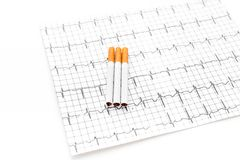 Danger of smoking. Cigarettes on cardiogram on white background Royalty Free Stock Image