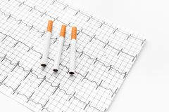 Danger of smoking. Cigarettes on cardiogram on white background Stock Photos