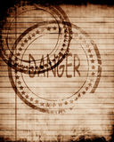Danger stamp on a grunge background Royalty Free Stock Photography