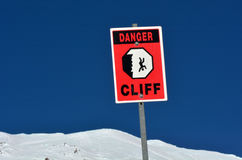 Danger steep cliff sign on snow cape mountain summit. Background Royalty Free Stock Images