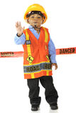 Danger.  Stop!. An adorable young road worker blowing a whistle and gesturing Stop! in his safety vest and hard hat.  He stands in front of a red Danger tape Royalty Free Stock Image