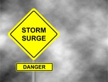 Danger storm surge road sign . Yellow hazard warning sign against grey sky   Stock Images
