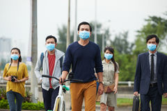 Danger of swine flu epidemic. Passers-by protected themselves from swine flu with help of masks while walking in Asian city Royalty Free Stock Photo