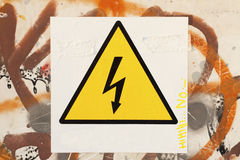 Danger symbol. Over a white cartel, over a wall with graffitti Stock Photography