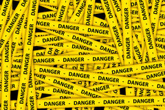 Danger Tape. Yellow caution tape strips with text of danger, on black background Royalty Free Stock Photos