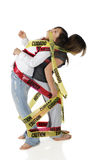 Danger: Teenage. Two young teen girls struggling to free themselves from the Danger and Caution tape they're wrapped in.  Isolated on white Royalty Free Stock Images