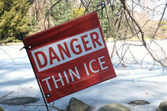 Danger Thin Ice. A read sign that reads Danger Thin Ice, next to a frozen pond Royalty Free Stock Photo