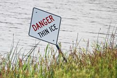 A danger thin ice sign along the shore in summer royalty free stock photo