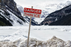 Danger thin ice sign. With Canadian rockies and the frozen Lake Louise in the background Stock Image