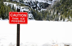 Danger thin ice sign with snowy lake Stock Photo