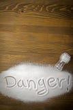 Danger of too much salt – Health Hazard. DANGER written on a heap of salt - Health Hazard royalty free stock image