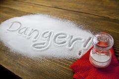 Danger of too much salt – Health Hazard. DANGER written on a heap of salt - Health Hazard royalty free stock images