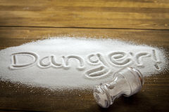 Danger of too much salt – Health Hazard. DANGER written on a heap of salt - Health Hazard royalty free stock photo