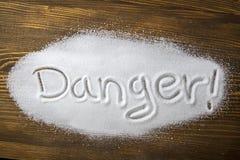 Danger of too much salt – Health Hazard. DANGER written on a heap of salt - Health Hazard royalty free stock photography
