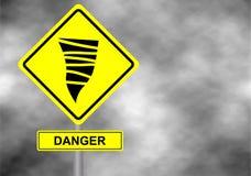 Danger tornado road sign . Yellow hazard warning sign against grey sky  Royalty Free Stock Images