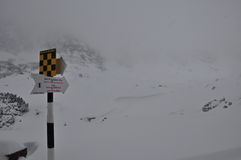 Danger. Tourist indicator with avalanche danger sign on the mountains in winter Stock Images