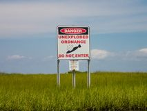 Danger unexploded ordnance do not enter posted above green sea stock photography