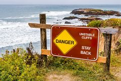 `Danger, unstable cliffs, stay back` sign. Posted on the Pacific Ocean coastline on an area with eroded cliffs and risk of landslide, California stock photography