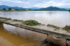 Damaged bridge across flowing river. Danger view with damaged bridge across flowing river in rainy season, old broken concrete bridge cross Kon river with many Royalty Free Stock Images