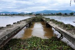 Damaged bridge across flowing river. Danger view with damaged bridge across flowing river in rainy season, old broken concrete bridge cross Kon river with many Royalty Free Stock Photo