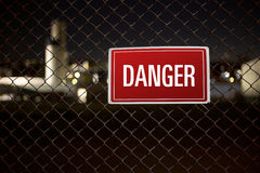 Danger warning sign hanging on a fence guarding private Stock Images