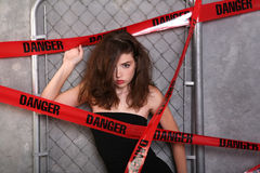 Danger Woman. Young Woman behind Danger Tape on Link Fence Royalty Free Stock Images