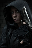Danger woman with gun. Dark colors Royalty Free Stock Photography