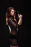 Danger woman with gun. Dark colors. Studio Stock Photo