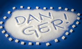 DANGER written with  sugar. Sugar on a blue background with warning message DANGER written on it. Health concept. Diabetes hazard Stock Images