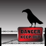 Danger zone. Abstract colorful background with fence made from barbed wire and a black crow standing on a warning plate. Danger keep out Stock Photo