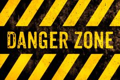 Danger zone warning sign text with yellow and black stripes painted over concrete wall surface facade cement texture background royalty free stock photo