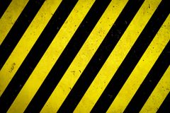 Danger Zone: Warning Sign Yellow And Black Stripes Painted Over Concrete Wall Coarse Facade With Holes And Imperfections Texture Stock Images