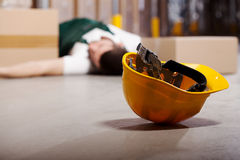 Dangerous accident during work. Dangerous accident in warehouse during work - wounded worker royalty free stock photo