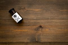 Dangerous addictions, dangerous entertainment. Poison. Bottle with skull and crossbones on dark wooden background top. View royalty free stock photography