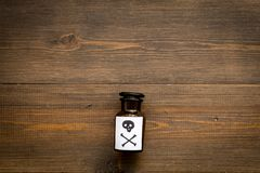 Dangerous addictions, dangerous entertainment. Poison. Bottle with skull and crossbones on dark wooden background top. View stock photo