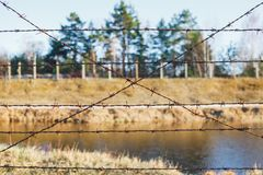 Dangerous area fenced with barbed wire fence royalty free stock photography