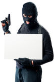 A dangerous armed bandit holding an inscription poster. On a white background Stock Image
