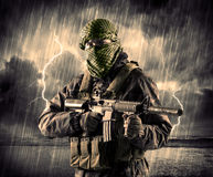 Dangerous armed terrorist with mask and gun in a thunderstorm wi. Portrait of a dangerous armed terrorist with mask and gun in a thunderstorm with lightning stock photography