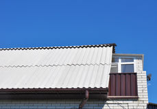 Dangerous asbestos new roof tiles with roof window, dormer and small balcony Royalty Free Stock Photo