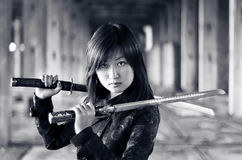 Dangerous asian girl. With katana in ruins royalty free stock photos