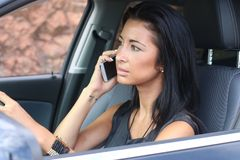 Dangerous attitude. Of a beautiful woman who phone while driving stock photography