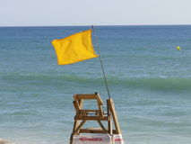 Dangerous beach. Beach with danger by the yellow flag and lack of the beach lifeguard. First aid station and caution flag Royalty Free Stock Photos