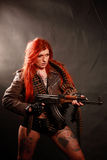 Dangerous beauty. Studio shot of young attractive redhead punk girl multiple tatto and rifle dressed in military style, taken against the wall covered by dark royalty free stock photography