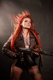 Dangerous beauty. Studio shot of young attractive redhead punk girl multiple tatto and rifle dressed in military style, taken against the wall covered by dark royalty free stock image