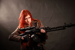 Dangerous beauty. Studio shot of young attractive redhead punk girl multiple tatto and rifle dressed in military style, taken against the wall covered by dark royalty free stock images