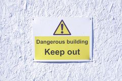 Dangerous building keep out warning caution sign on white wall at construction building site. Dangerous building keep out sign on white wall at construction Royalty Free Stock Photography