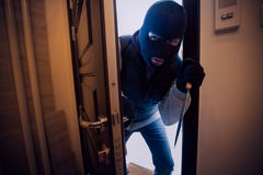 Dangerous burglar sneaking into the house. With a knife in his hand royalty free stock photography